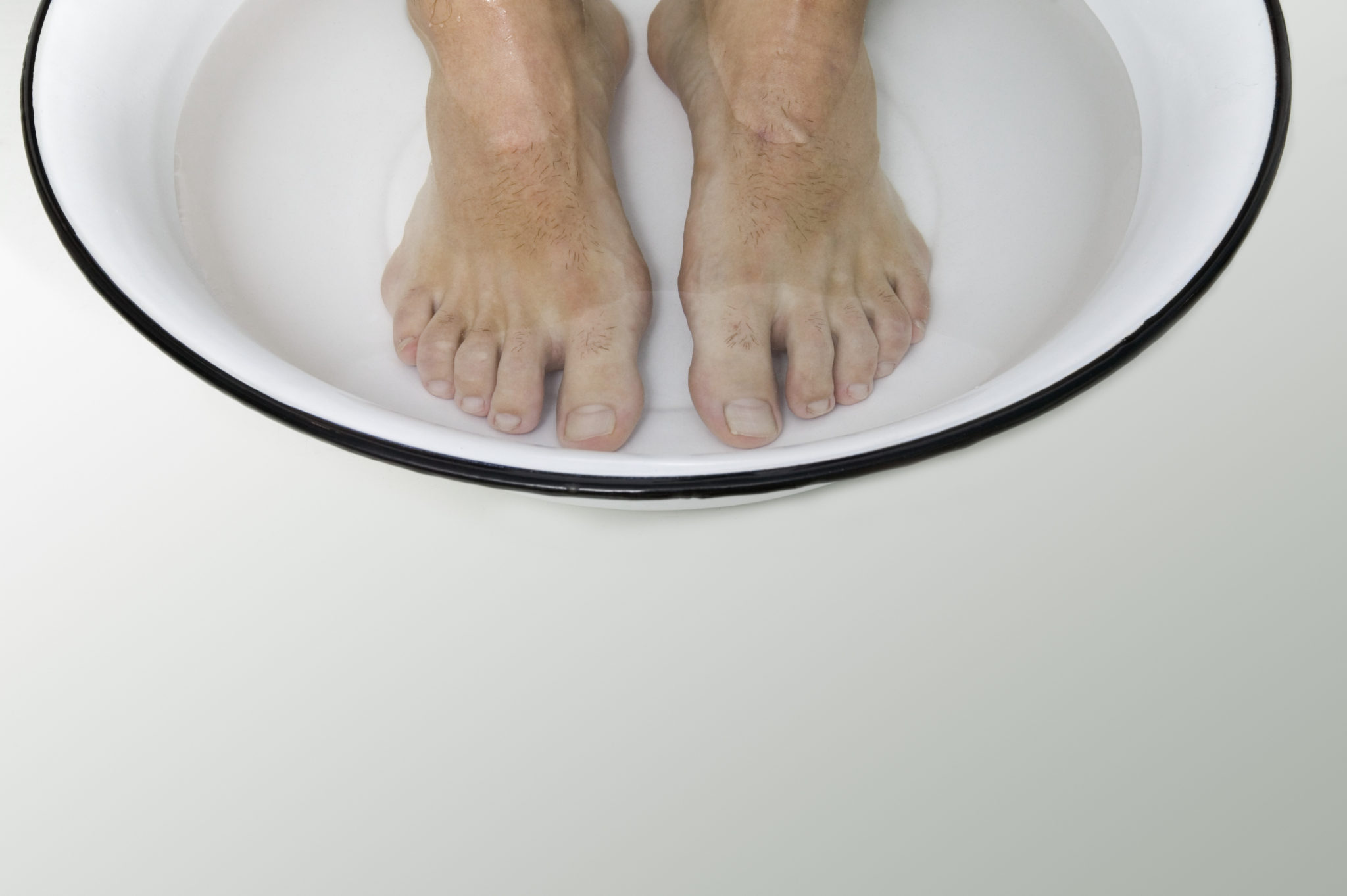 High angle view of a man's feet in a bowl of water
